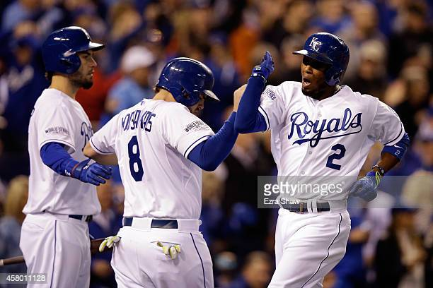 Alcides Escobar of the Kansas City Royals celebrates with Mike Moustakas after scoring in the second inning against the San Francisco Giants during...