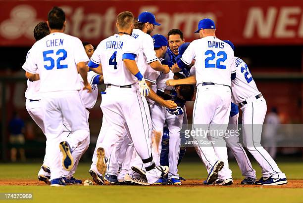 Alcides Escobar of the Kansas City Royals is congratulated byteammates after hitting a double to knock in the winning run during the bottom of the...