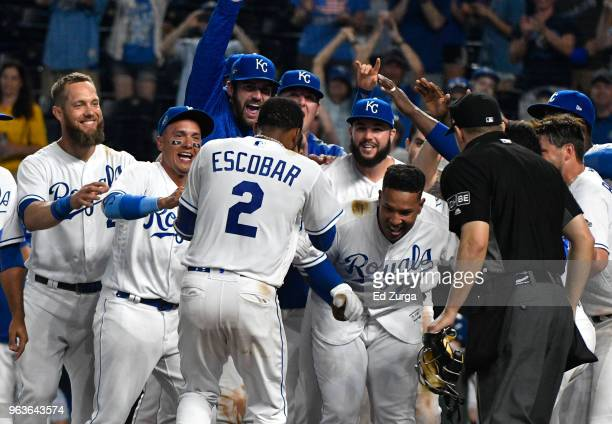 Alcides Escobar of the Kansas City Royals is congratulated by teammates after hitting a walkoff home run in the 14th inning against the Minnesota...