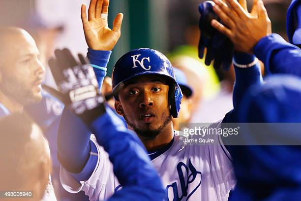 Alcides Escobar of the Kansas City Royals is congratulated by teammates in the dugout after scoring a run in the third inning against the Toronto...