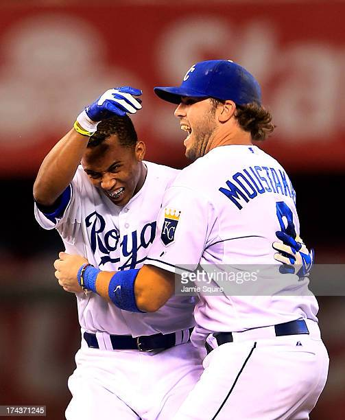 Alcides Escobar of the Kansas City Royals is congratulated by Mike Moustakas after Escobar hit a double to knock in the winning run during the bottom...