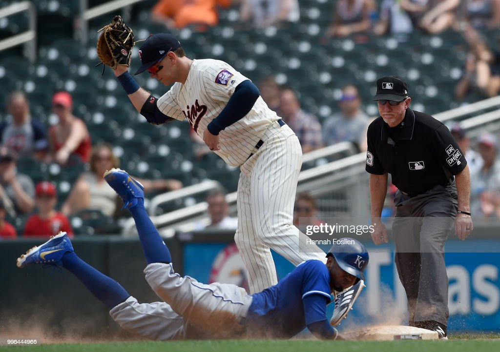 Alcides Escobar #2 of the Kansas City Royals is out at first base as Logan Morrison #99 of the Minnesota Twins fields the ball and umpire Lance Barksdale #23 looks on during the eighth inning of the game on July 11, 2018 at Target Field in Minneapolis, Minnesota. The Twins defeated the Royals 8-5.