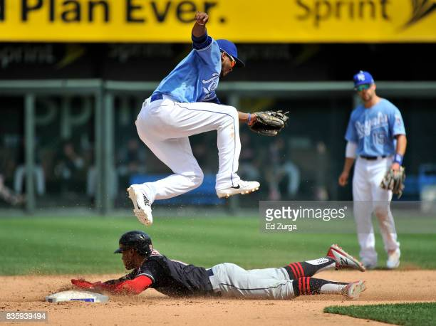 Alcides Escobar of the Kansas City Royals leaps over Francisco Lindor of the Cleveland Indians as Lindor slides safely into second for a steal in the...