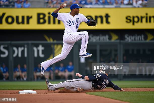 Alcides Escobar of the Kansas City Royals leaps over Jonathan Lucroy of the Milwaukee Brewers as he throws to first on a double play attempt at...