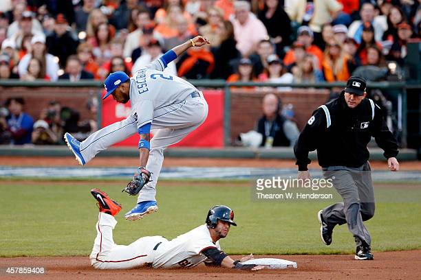 Alcides Escobar of the Kansas City Royals leaps to catch a ball as Gregor Blanco of the San Francisco Giants advances on a wild pitch in the first...