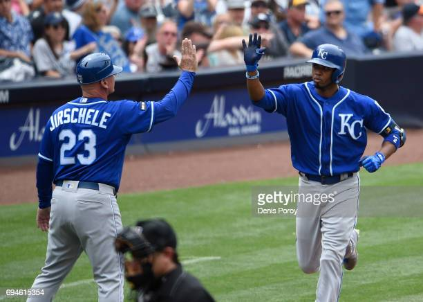 Alcides Escobar of the Kansas City Royals right is congratulated by Mike Jirschele after hitting a solo home run during the fifth inning of a...