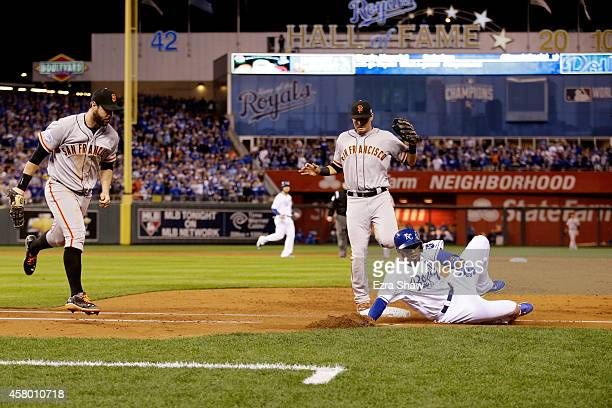 Alcides Escobar of the Kansas City Royals slides into first base safely in front of the tag of Brandon Belt of the San Francisco Giants as Joe Panik...