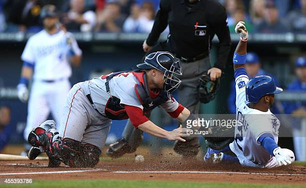 Alcides Escobar of the Kansas City Royals slides into home to score past Christian Vazquez of the Boston Red Sox on a Norichika Aoki single in the...