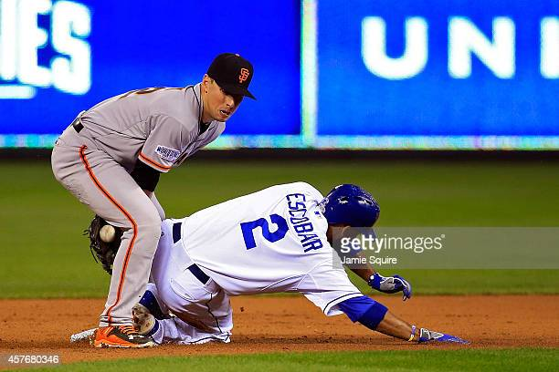 Alcides Escobar of the Kansas City Royals slides safely into second base as Joe Panik of the San Francisco Giants tries to make the play during Game...