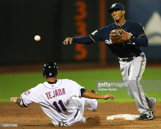 Alcides Escobar of the Milwaukee Brewers completes a double play while Ruben Tejada of the New York Mets is unsuccessful sliding into second base on...