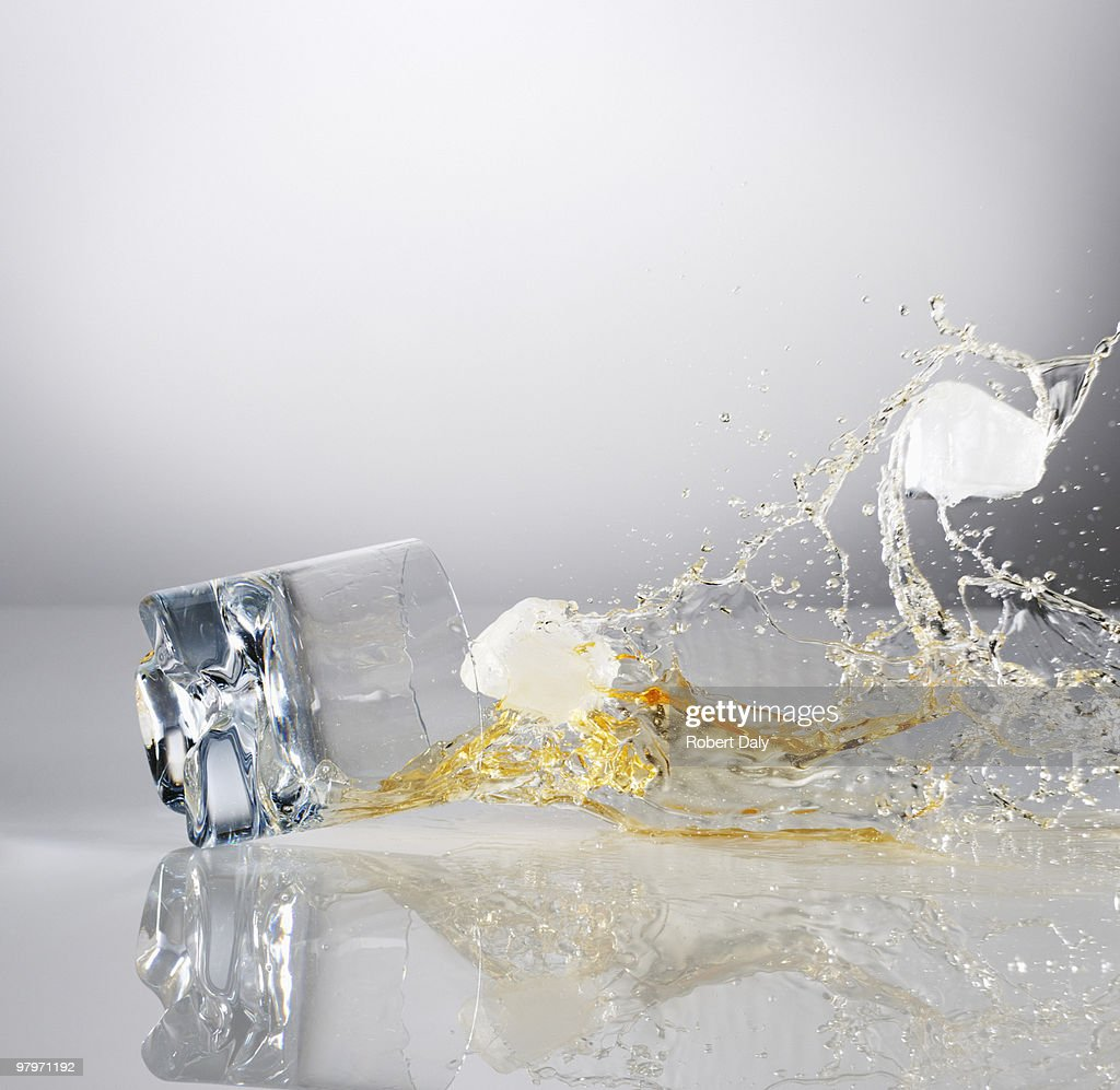 Alcohol and ice cubes spilling from falling highball glass : Stock Photo