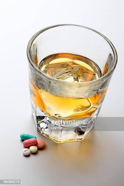 Alcohol y medicamentos recetados sobre fondo gris claro