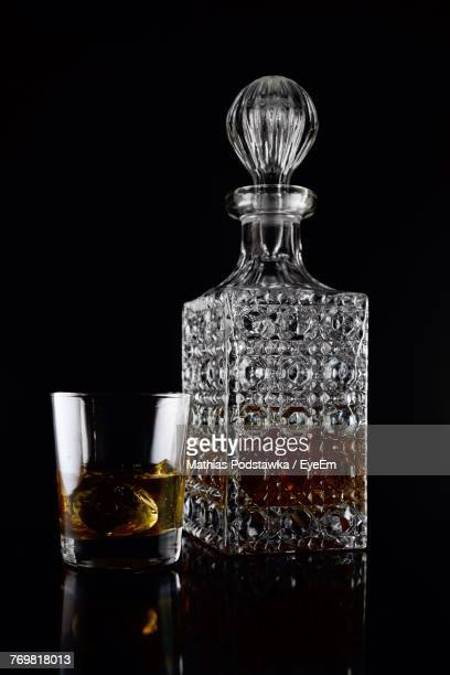 alcohol bottle with drinking glass against black background - liqueur stock pictures, royalty-free photos & images