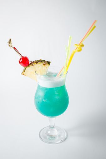 Alcohol fresh blue curacao coctail with pineapple and berry on white background - gettyimageskorea