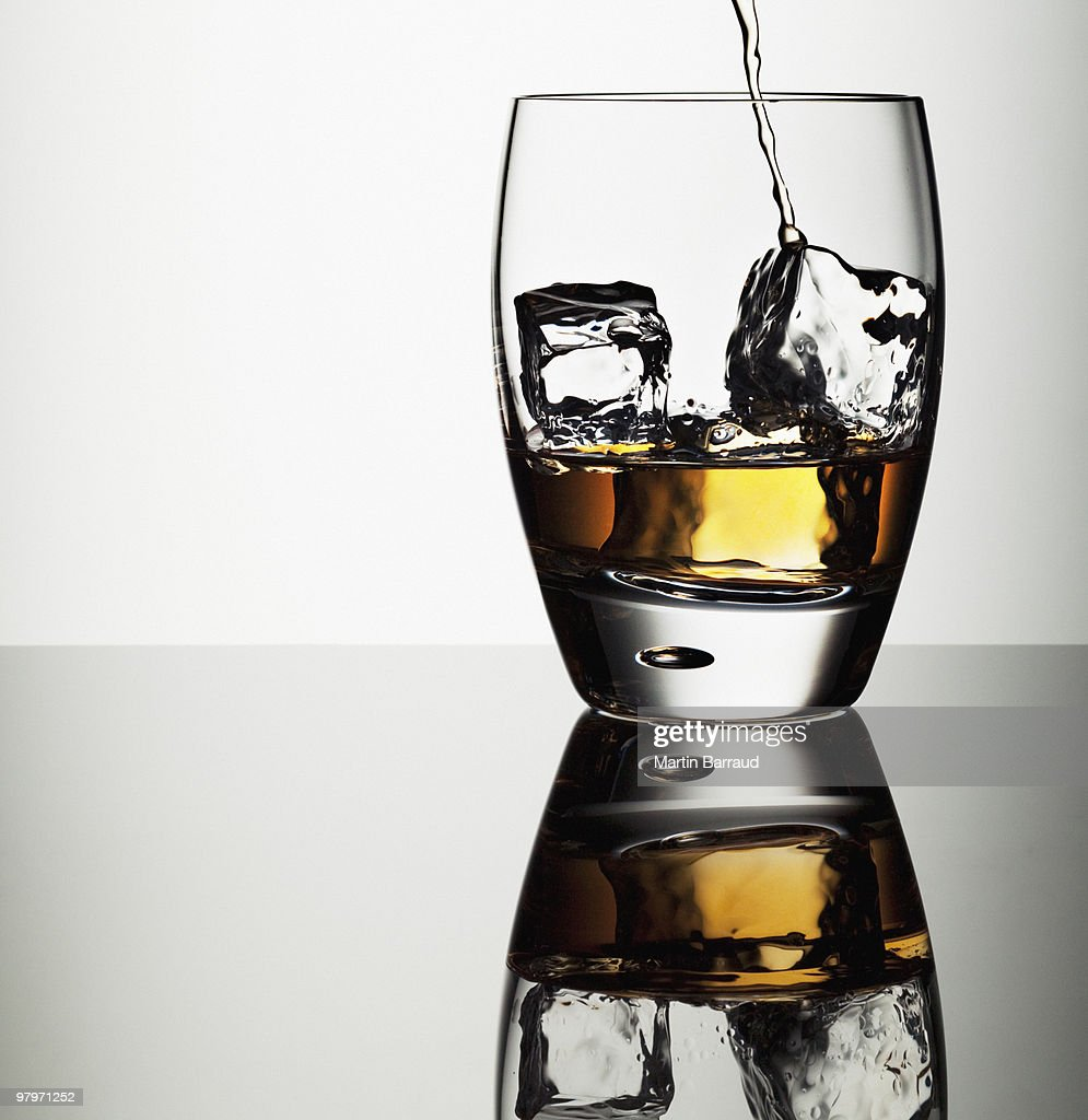 Alcohol pouring into highball glass with ice cubes : Stock Photo