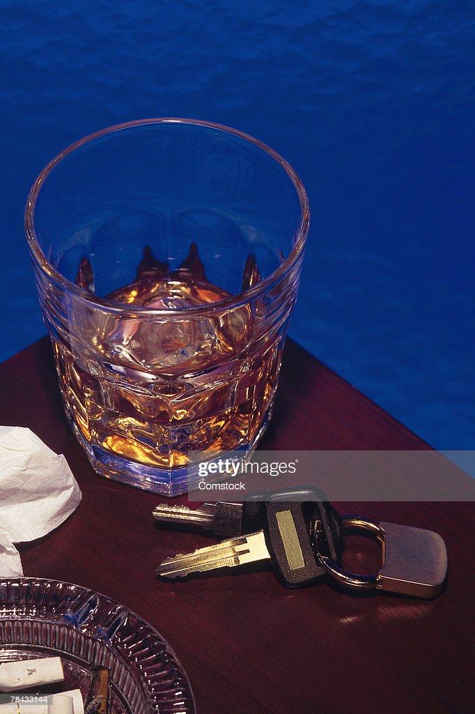 Alcoholic beverage next to car keys symbolizes drunk driving : Stockfoto