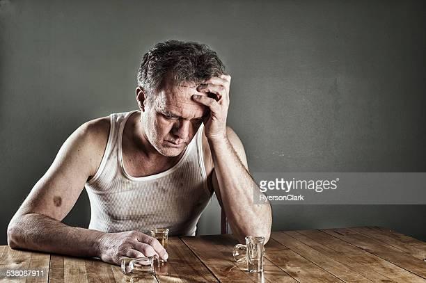 Alcoolisme.   Un homme buvant à une Table, Ivre.