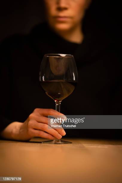 Alcoholism symbol photo: A woman sitting alone at home at a table with a glass of red wine on January 23, 2021 in Berlin, Germany.