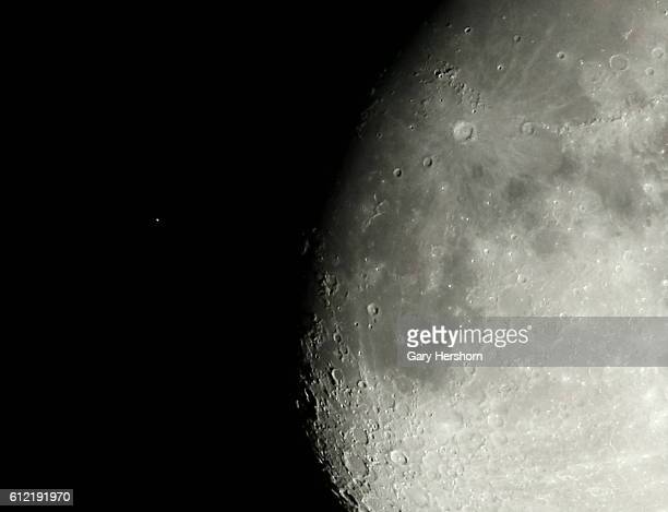 Aldebaran the brightest star in the constellation of Taurus is seen to the left of the moon before its occulation in the night sky as seen from...