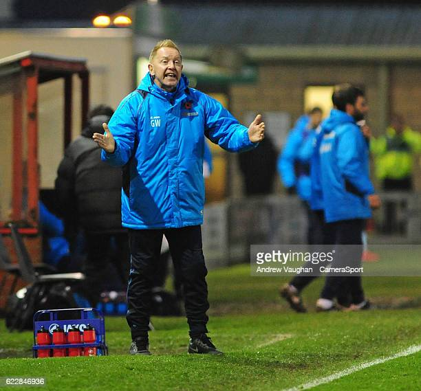 Aldershot Town manager Gary Waddock shouts instructions to his team from the dugout during the Vanarama National League match between Lincoln City...
