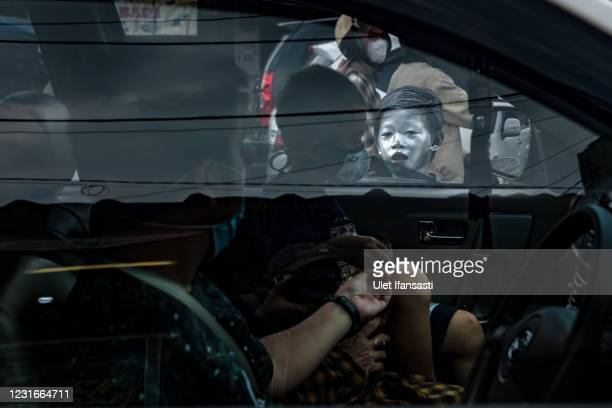 """Aldi , wearing silver paint begging for money on the street on March 11, 2021 in Depok, Indonesia. 'Silver Men', called """"Manusia Silver"""" in..."""