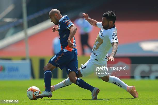 Aldo Arellano of Queretaro struggles for the ball with Alan Mendoza of Pumas during the 11th round match between Pumas UNAM and Puebla as part of the...