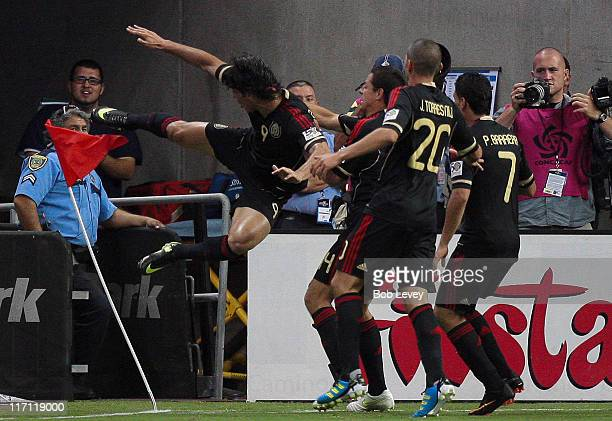 Aldo De Negris of Mexico kicks the corner flag as he celebrates with Jorge Torres Nilo and Pablo Barrera after scoring in the first overtime period...