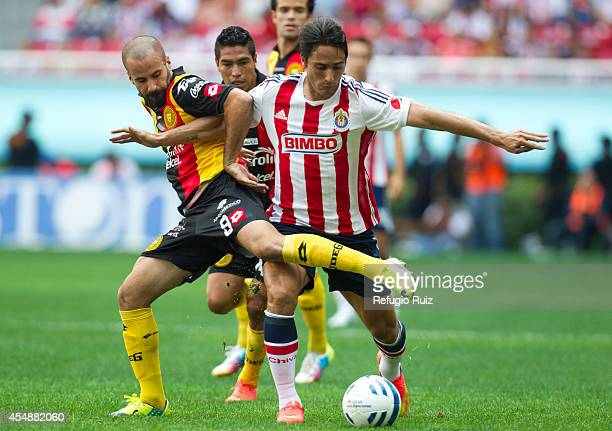 Aldo de Nigris of Chivas fights for the ball with Marc Crosas of Leones Negros during a match between Chivas and Leones Negros as part of 3rd round...