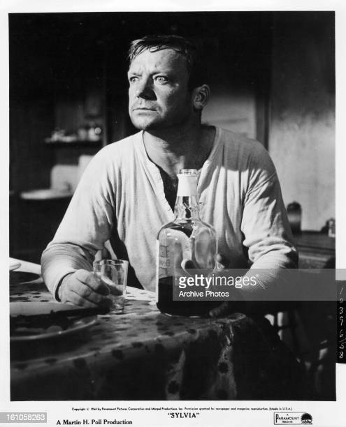Aldo Ray drink a bottle of hard liquor in scene from the film 'Sylvia' 1965
