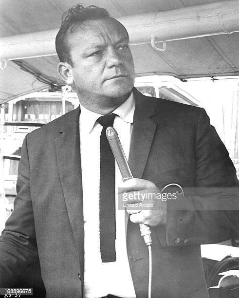 Aldo Ray holds a microphone in a scene from the film 'Kill A Dragon' 1967
