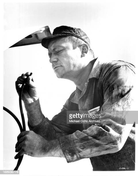 Aldo Ray is focused on a hose in a scene from the film 'The Power' 1968