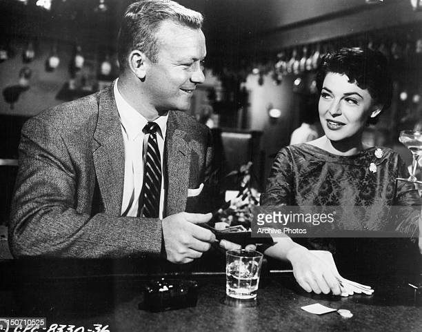 Aldo Ray opening his wallet to Anne Bancroft in a scene from the film 'Nightfall' 1957
