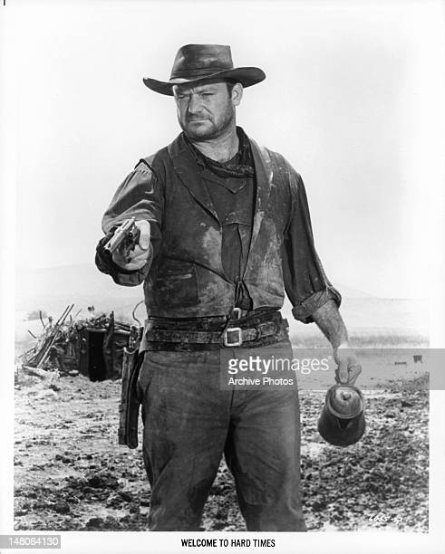 Aldo Ray wearing western attire pointing a gun in a scene from the film 'Welcome To Hard Times' 1967