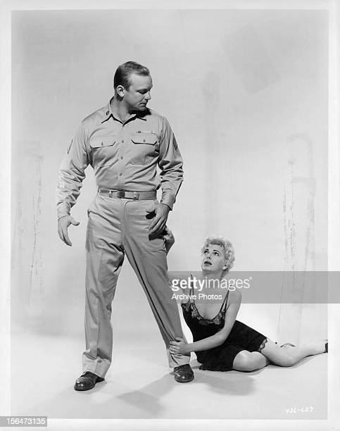 Aldo Ray's leg is grabbed by Barbara Nichols in publicity portrait for the film 'The Naked And The Dead' 1958
