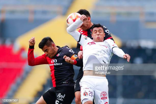Aldo Rocha of Atlas jumps for the ball with Edgar López of Tijuana during the 13th round match between Atlas and Club Tijuana as part of the Torneo...
