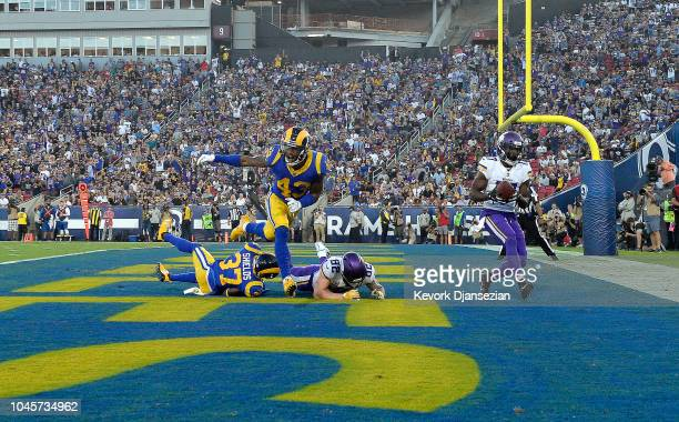 Aldrick Robinson of the Minnesota Vikings scores a touchdown as safety John Johnson III of the Los Angeles Rams reacts during the first half at Los...