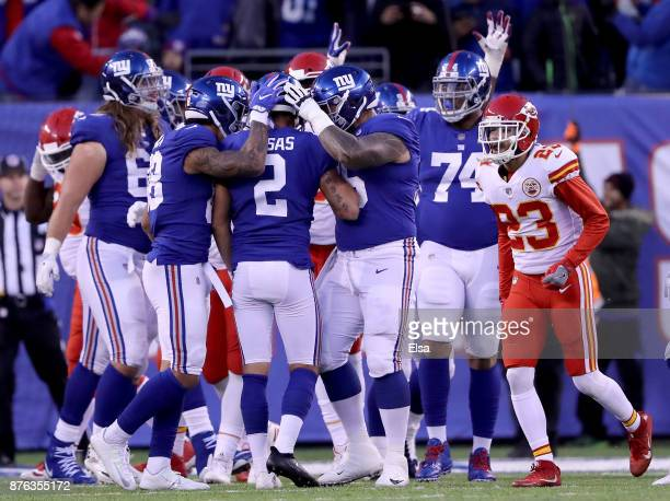 Aldrick Rosas of the New York Giants is congratulated by teammates Evan Engram and Jon Halapio of the New York Giants after Rosas kicked the game...