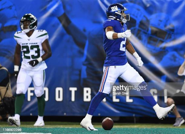Aldrick Rosas of the New York Giants reacts after scoring a touchdown while Godwin Igwebuike of the New York Jets looks on during the fourth quarter...