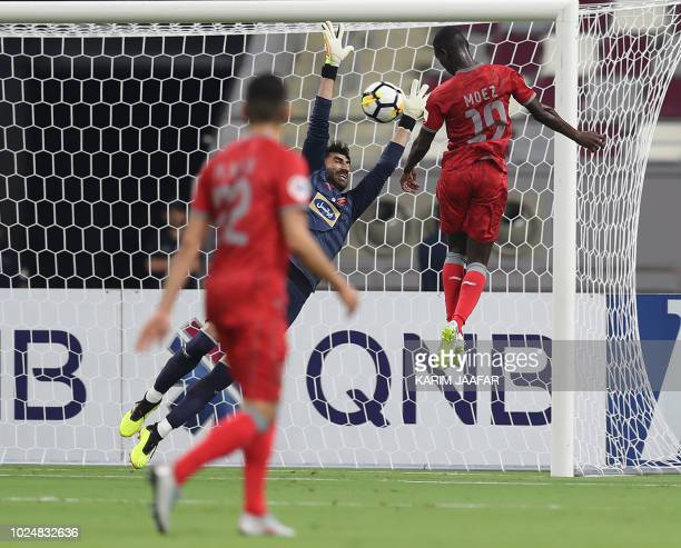 AlDuhail SC's Qatari forward Almoez Ali heads a goal against Persepolis FC's Iranian goalkeeper Alireza Beiranvand during the AFC Champions League...