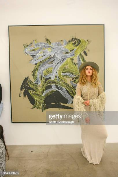 Alea Remains poses in front of a painting by Brandon Boyd while at OptiMystic A Brandon Boyd Pop Up Gallery Featuring He Tasya Van Ree Natalie...