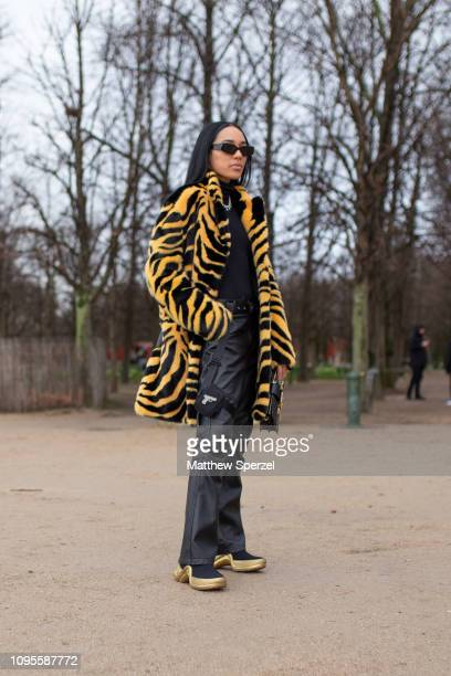 Aleali May is seen attending Louis Vuitton during Men's Paris Fashion Week AW19 wearing tiger print fur coat black and gold shoes on January 17 2019...