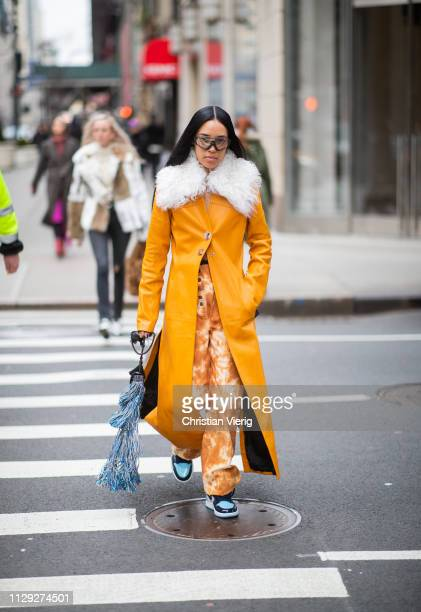 Aleali May is seen wearing orange coat with faux fur collar bag with fringes outside 31 Phillip Lim during New York Fashion Week Autumn Winter 2019...