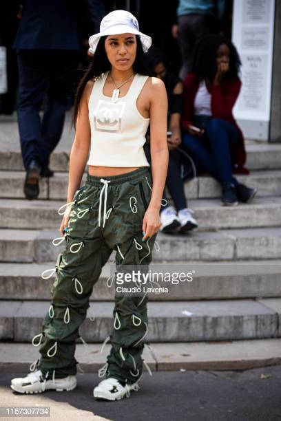 Aleali May, wearing a cream Chanel tank top, green decorated pants, white sneakers and white hat, is seen outside Rick Owens fashion show on Day 3...