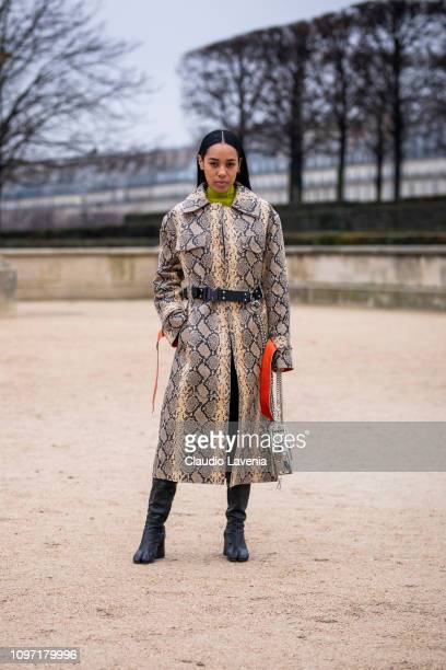 Aleali May wearing a long snake print coat black boots and see through bag is seen in the streets of Paris before the Kenzo show on January 20 2019...
