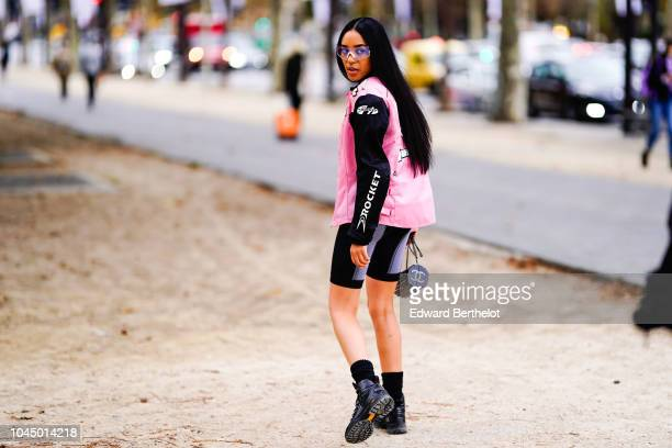Aleali May wears a black and pink jacket a cropped top short leggings outside Chanel during Paris Fashion Week Womenswear Spring/Summer 2019 on...