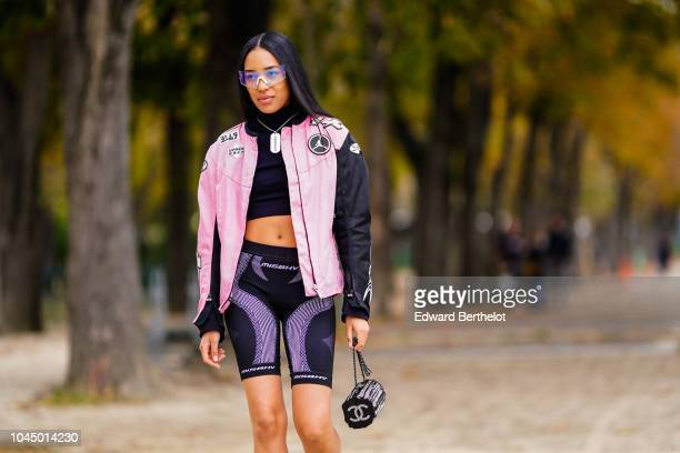 Aleali May wears a black and pink jacket, a cropped top, short leggings, outside Chanel, during Paris Fashion Week Womenswear Spring/Summer 2019 on...