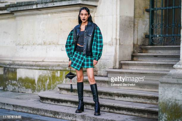 Aleali May wears a black leather jacket with green checkered pattern print large sleeves, a black crop top, a skirt, black leather thigh high boots,...