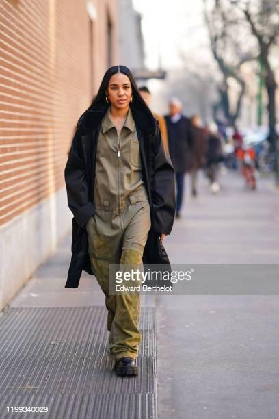 Aleali May wears a black long coat, a green khaki jumpsuit, black shoes, earrings, outside Fendi, during Milan Fashion Week Menswear Fall/Winter...