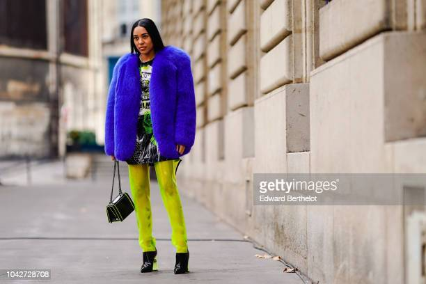 Aleali May wears a blue fluffy coat yellow pants a Balmain bag outside Balmain during Paris Fashion Week Womenswear Spring/Summer 2019 on September...