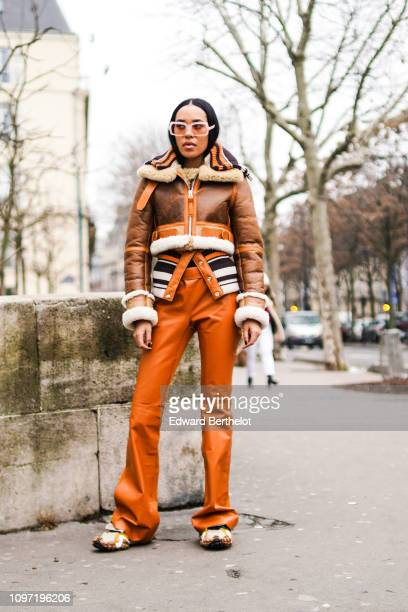 Aleali May wears a brown leather aviator jacket orange flare pants black and white striped wool top outside Acne during Paris Fashion Week Menswear...